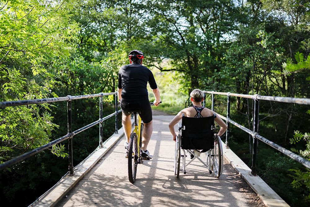 Man op fiets naast vrouw in rolstoel