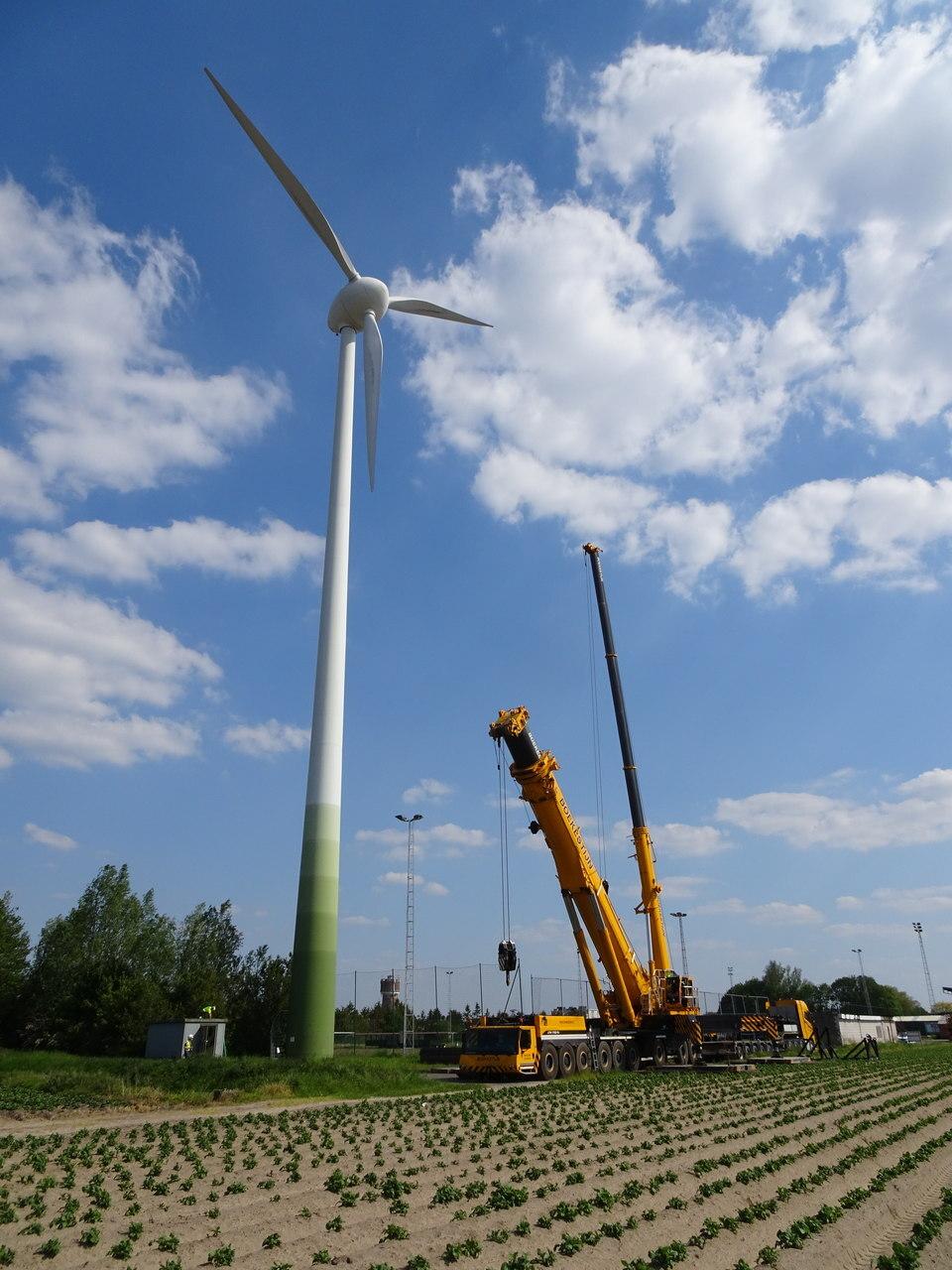 Foto: de kraan staat klaar om – als er niet te veel wind is – op 2 juni 2021 de windturbine aan de het voetbalveld in Eeklo te demonteren. In de 141322 uur dat de windturbine aan het voetbalveld draaide, produceerde ze 17.301.086 kWh aan lokale groene burgerstroom. Een mooie carrière ten dienste van de coöperanten die de windstroom thuis gebruiken!